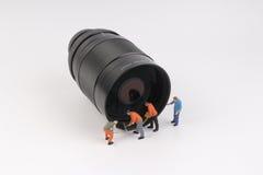 Mini ature woker rozjaśnia obiektyw Zdjęcie Royalty Free