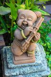 Mini baby playing musical instrument  statuary. In the garden Royalty Free Stock Photo