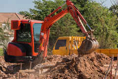 Mini backhoe. Dig the ground hole for build new house royalty free stock photo