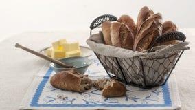 Mini- bagett i tappningkorg med smör och honung Arkivfoton