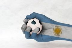 Mini ball of football in Argentina flag painted hand on white background. Concept of sport or the game in handle or minor matter stock photos