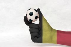 Mini ball of football in Belgium flag painted hand, hold it with two finger on white background. tricolor of black yellow and red. Concept of sport or the game stock photography