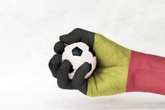 Mini ball of football in Belgium flag painted hand on white background.Concept of sport or the game in handle or minor matter. Mini ball of football in Belgium stock photography