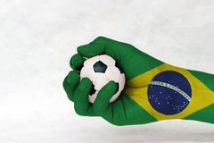 Mini ball of football in Brazil flag painted hand on white background. Concept of sport or the game in handle or minor matter. royalty free stock photography
