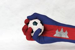 Mini ball of football in Cambodia flag painted hand on white background.