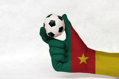 Mini ball of football in Cameroon flag painted hand on white background. stock photos