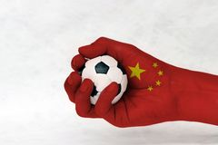 Mini ball of football in China flag painted hand on white background.Concept of sport or the game in handle or minor matter. Mini ball of football in China flag royalty free stock images