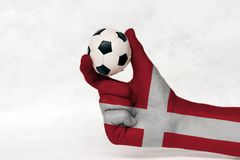 Mini ball of football in Denmark flag painted hand, hold it with two finger on white background. Concept of sport or the game in handle or minor matter stock photos