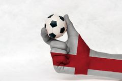 Mini ball of football in England flag painted hand on white background. Concept of sport or the game in handle or minor matter royalty free stock image