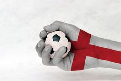 Mini ball of football in England flag painted hand on white background. Concept of sport or the game in handle or minor matter. Mini ball of football in England royalty free stock photos