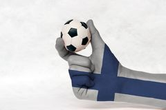 Mini ball of football in Finland flag painted hand, hold it with two finger on white background. Concept of sport or the game in handle or minor matter royalty free stock photography