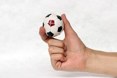 Mini ball of football in hand and one black point is Denmark flag, hold it with two finger on white background. Concept of sport or the game in handle or minor royalty free stock photos