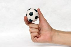 Mini ball of football in hand, hold it with two finger on white background. royalty free stock photography