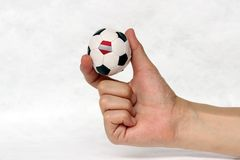 Mini ball of football in hand and one black point of football is Austria flag, hold it with two finger on white background. Concept of sport or the game in stock image
