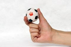 Mini ball of football in hand and one black point of football is China flag, hold it with two finger on white background. Concept of sport or the game in royalty free stock images