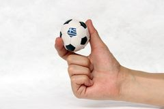 Mini ball of football in hand and one black point of football is Greece flag, hold it with two finger on white background. Concept of sport or the game in royalty free stock photography