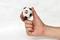 Mini ball of football in hand and one black point of football is Hungary flag, hold it with two finger on white background. Concept of sport or the game in stock image