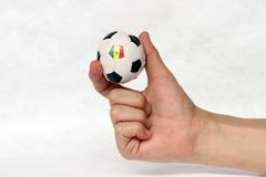 Mini ball of football in hand and one black point of football is Senegal flag, hold it with two finger on white background. Concept of sport or the game in stock photography