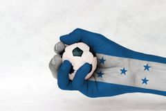 Mini ball of football in Honduras flag painted hand on white background. Concept of sport or the game in handle or minor matter. A horizontal triband of blue stock image