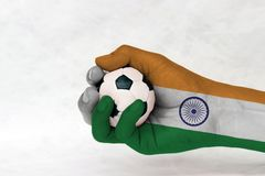 Mini ball of football in India flag painted hand on white background. stock photo