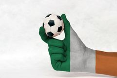 Mini ball of football in Ireland flag painted hand on white background. Concept of sport or the game in handle or minor matter stock images