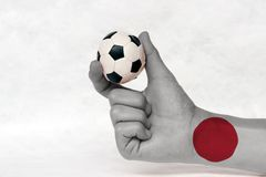 Mini ball of football in Japan flag painted hand, hold it with two finger on white background. Red circle sun on white. Concept of sport or the game in handle royalty free stock image