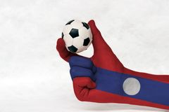 Mini ball of football in Laos flag painted hand, hold it with two finger on white background. stock photos