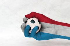 Mini ball of football in Luxembourg flag painted hand on white background stock images