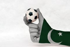 Mini ball of football in Pakistan flag painted hand, hold it with two finger on white background. royalty free stock image