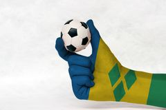 Mini ball of football in Saint Vincent flag painted hand, hold it with two finger on white background. stock photo