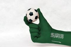 Mini ball of football in Saudi Arabia flag painted hand, hold it with two finger on white background. Concept of sport or the game in handle or minor matter stock images