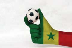 Mini ball of football in Senegal flag painted hand, hold it with two finger on white background. Concept of sport or the game in handle or minor matter. green stock photography