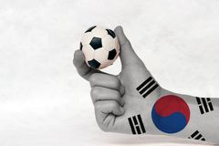 Mini ball of football in South Korea flag painted hand, hold it with two finger on white background. royalty free stock photos