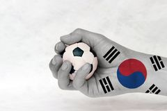 Mini ball of football in South Korea flag painted hand on white background. Concept of sport or the game in handle or minor matter. the white color with stock photography