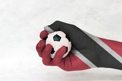 Mini ball of football in Trinidad and Tobago flag painted hand on white background. Concept of sport or the game in handle. stock photo