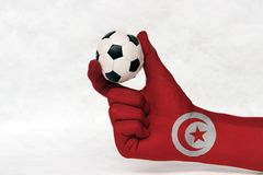 Mini ball of football in Tunisia flag painted hand, hold it with two finger on white background. Concept of sport or the game in handle or minor matter stock photography