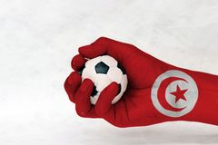 Mini ball of football in Tunisia flag painted hand on white background. Concept of sport or the game in handle or minor matter. Mini ball of football in Tunisia stock images