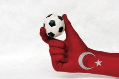 Mini ball of football in Turkey flag painted hand, hold it with two finger on white background. Concept of sport or the game in handle or minor matter royalty free stock images