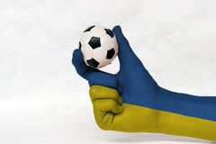 Mini ball of football in Ukraine flag painted hand, hold it with two finger on white background. stock image