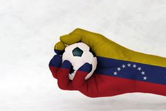 Mini ball of football in Venezuela flag painted hand on white background. Concept of sport or the game in handle or minor matter royalty free stock photography