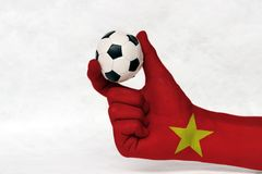 Mini ball of football in Vietnam flag painted hand, hold it with two finger on white background. Concept of sport or the game in handle or minor matter royalty free stock image