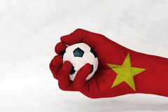 Mini ball of football in Vietnam flag painted hand on white background. Concept of sport or the game in handle or minor matter stock photo