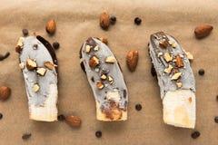 Mini bananas congeladas com cobertura em chocolate com amêndoas Imagens de Stock Royalty Free