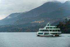 Mini bateau de croisière se déplaçant lentement le lac avec pluvieux photos stock
