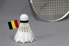 Mini Belgium flag stick on the white shuttlecock on the grey background and out focus badminton racket. Concept of badminton sport stock photo