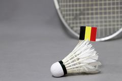 Mini Belgium flag stick on the white shuttlecock on the grey background and out focus badminton racket. Concept of badminton sport stock image