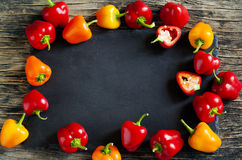 Mini Bell Peppers on wooden background with black board stock photography