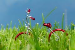 mini bici roja del juguete en hierba Fotos de archivo