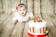 Cute 6 months baby girl. Mini birthday with strawberry theme. Cute 6 months baby girl with a sweet party cake royalty free stock photos