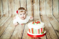 Cute 6 months baby girl. Mini birthday with strawberry theme. Cute 6 months baby girl with a sweet party cake stock photography